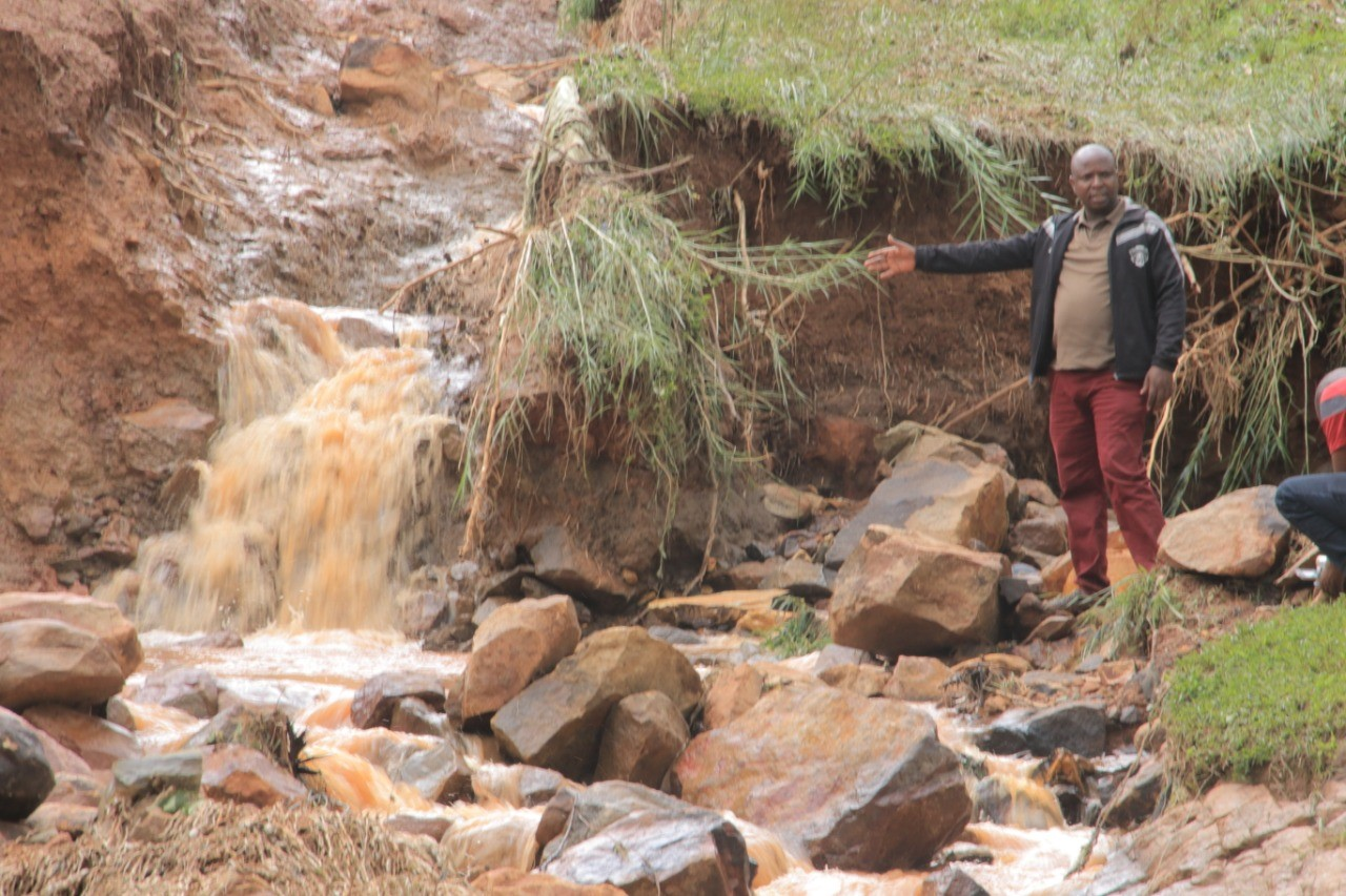 Area MCA Paul Angwenyi showing Journalists how waters had deeply cut the soil on Friday