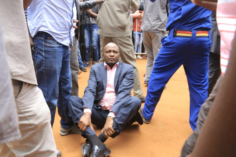 MP Moses Kuria opts to sit down on dust after he was roughed up by angry mob  in Kitui during the BBI forum Photo/Courtesy
